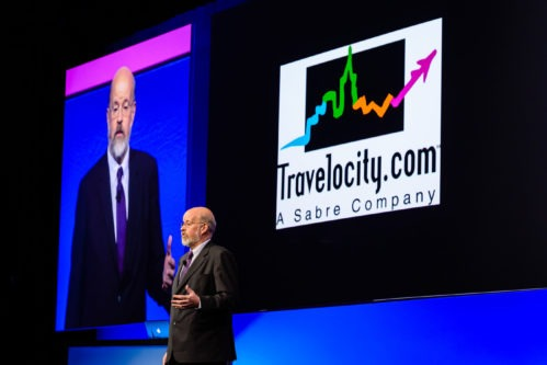 Terry Jones standing in front of a slide, presenting a picture of Travelocity